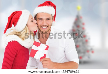 Young festive couple against blurry christmas tree in room - stock photo