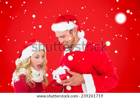 Young festive couple against red background - stock photo