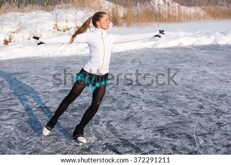 young Figure skating woman at the frozen lake in the winter
