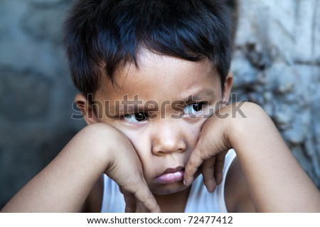 Young Filipino boy portrait against wall - sad expression, poverty - stock photo