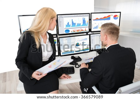 Young financial workers analyzing graphs on desktop computers at desk in office - stock photo