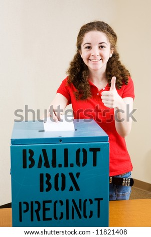 Young first time voter casting her ballot and giving a thumbs-up sign. - stock photo