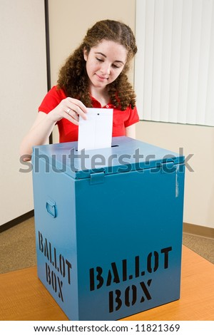 Young first time voter dropping her ballot in the box at the polling place. - stock photo
