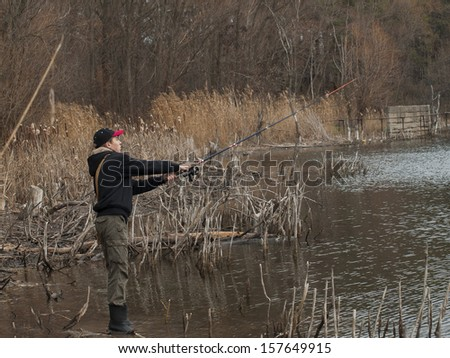 Young fisherman catches a fish pond on the old spinning - stock photo