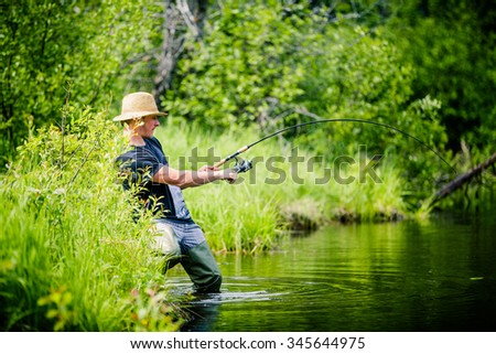 Young Fisherman Catching a big Fish into a Freshwater creek