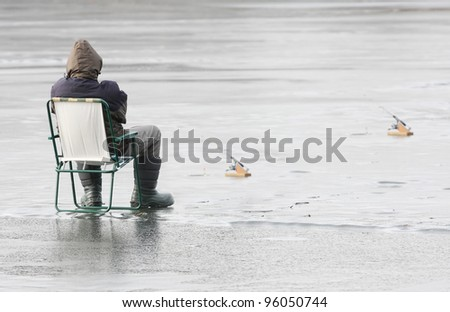 Young fisherman catching a fish on a frozen lake in winter. - stock photo
