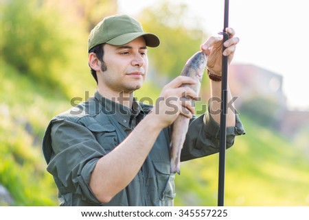 Young fisherman fishing in the river - stock photo