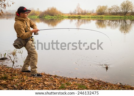 Young fisherman fishing on the river bank. Professional fisherman holding a spinning fish on a hook. Playing a fish. The concept of a country holiday.