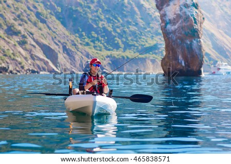 Young Fisherman in a Kayak. Fishing Boat in the sea.