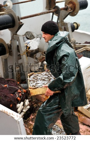 Young fisherman, on board a trawler boat and under rainy weather, carrying a wooden box full of small fish - stock photo