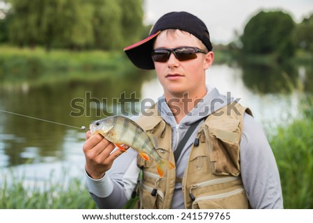Young fisherman on the river bank. Fisherman caught a perch and holds it in his hands. - stock photo