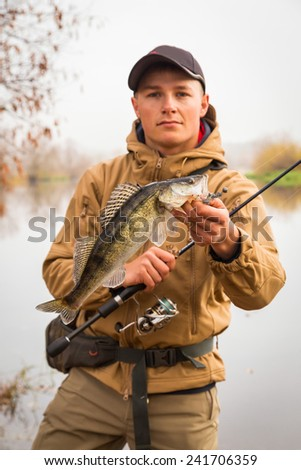 Young fisherman on the river bank. Fisherman caught a zander and holds it in his hands. - stock photo