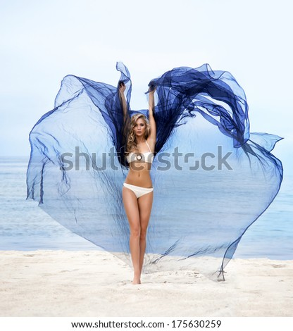 Young, fit and beautiful woman on the beach dancing with a blowing silk - stock photo
