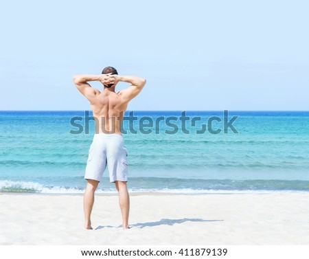 Young, fit and handsome man with athletic and muscled body standing on a summer beach - stock photo