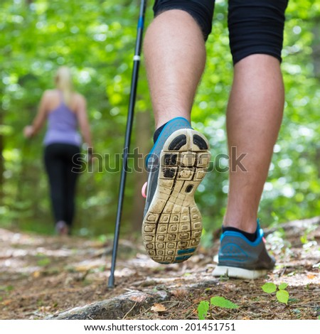 Young fit couple hiking in nature. Adventure, sport and exercise. Detail of male step, legs and nordic walking poles in green woods. - stock photo