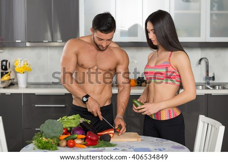 young fit couple in the kitchen, cooking, cutting vegetables - stock photo