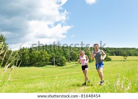 Young fit couple jogging on summer day in meadows countryside