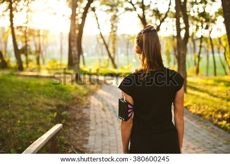 Young fit girl athlete standing in park before evening training with arm band listening to music on her phone with earphones. Sunset on background. Half length view from behind with copy space - stock photo