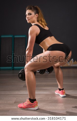 Young fit girl doing exercises with dumbells in gym - stock photo