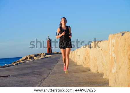 Young fit girl is running alone at beautiful sunset near the sea. Summer sport, freedom concept and healthy lifestyle.