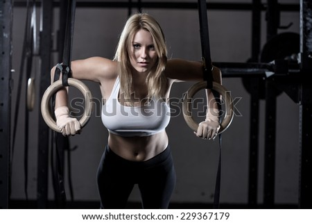 Young fit girl pulling up on a gimnastic rings - stock photo
