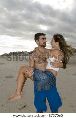 Young, fit, happy couple in the beach. Man holding girl. - stock photo