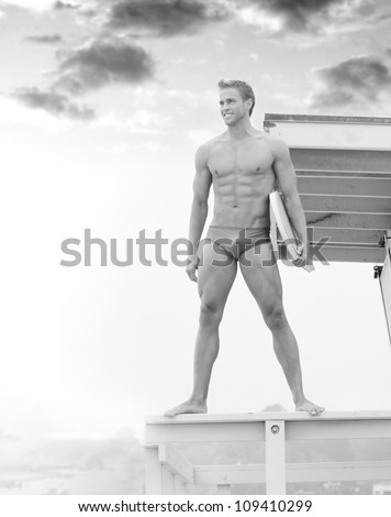 Young fit lifeguard on duty at the beach standing on tower - stock photo