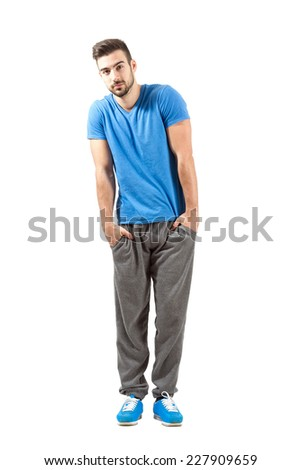 Young fit male in sport outfit with hands in pocket looking at camera. Full body length portrait isolated over white background. - stock photo