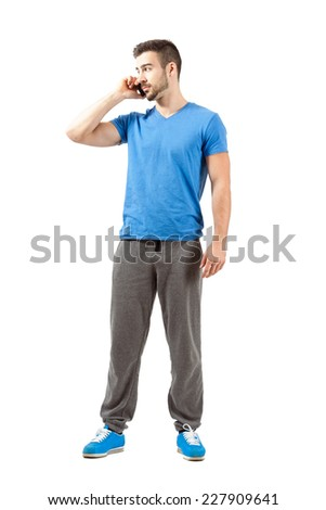 Young fit male in sweatpants talking on the phone looking away. Full body length portrait isolated over white background. - stock photo