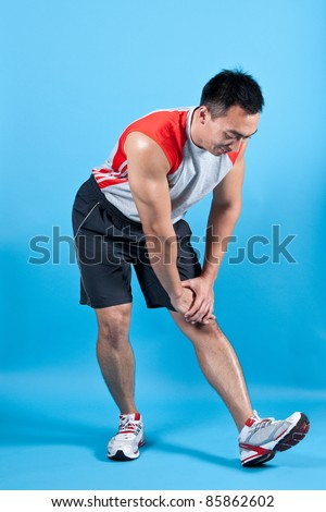 Young fit man doing hamstring stretch - stock photo