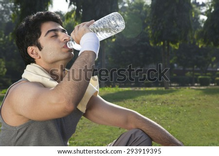 Young fit man drinking water after sport workout - stock photo
