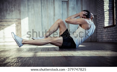 Young fit man exercising in a gym - stock photo