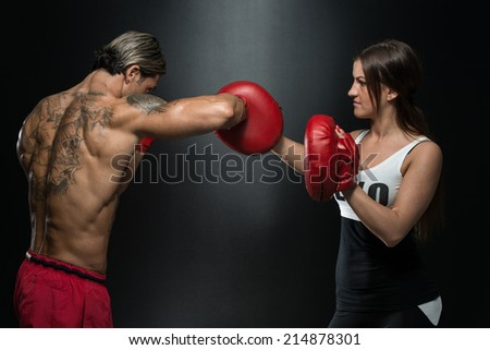 Young Fit Man Fighting A Woman - Bodybuilding Couple Posing With Boxing Gloves On Black Background