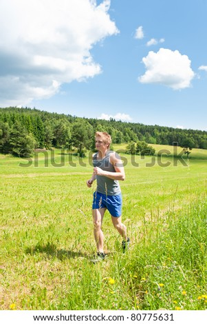 Young fit man jogging on summer day in meadows countryside