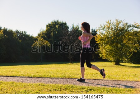 Young fit woman does running, jogging training in a park during sunset - stock photo