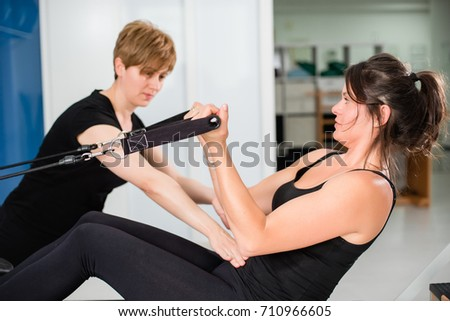 Young fit woman doing complicated exercises on pilates reformer bed with female instructor at empty gym. Sports equipment. Active and healthy lifestyle