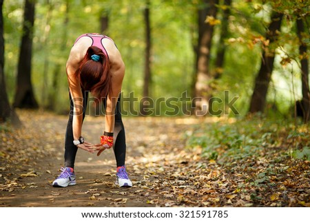 young fit woman doing exercise in park, rear view - stock photo