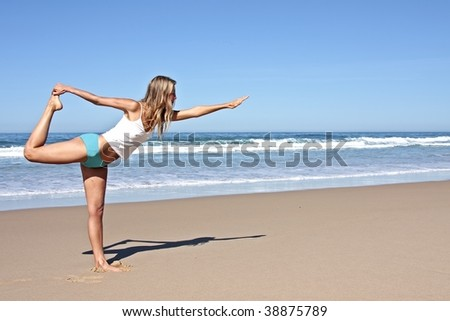 Young fit woman doing exercises on the beach - stock photo