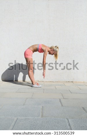 Young fit woman dressed in sports wear stretches body muscles while standing against street wall background with copy space area for your text message or content, athletic female working out outdoors - stock photo