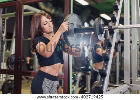 Young fit woman in the gym loading weights on the barbell in the squat rack  - stock photo