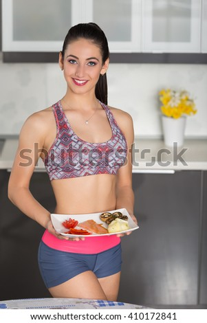 young fit woman in the kitchen, preparing healthy meal: one plate with salmon, mushrooms, potatoes, tomato and red pepper - stock photo