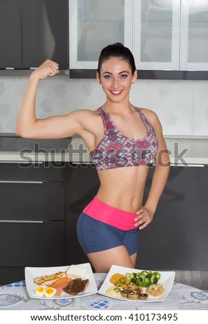 young fit woman in the kitchen, showing her biceps; animal versus plant proteins:  plate with beef, eggs, salmon, cheese and chicken grill and nuts, mushrooms, broccoli, lentil, hummus and quinoa