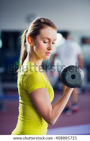 Young fit woman lifting dumbbell in gym