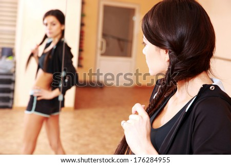Young fit woman looking at her reflection in mirror at gym - stock photo