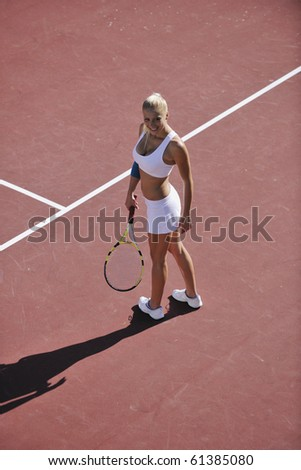 young fit woman play tennis outdoor on orange tennis field at early morning