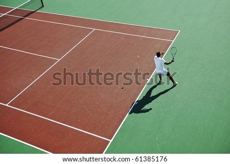 young fit woman play tennis outdoor on orange tennis field at early morning - stock photo