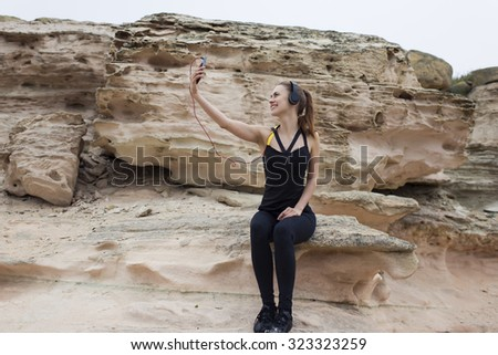 Young fit woman using mobile phone while talking with her friend about active sport life and beautiful nature around, attractive female runner taking break after workout and photographing herself - stock photo