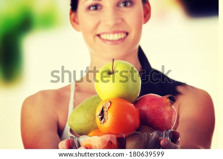 Young fit woman with bowl of exotic fruits