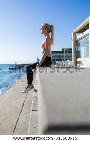 Young fit woman with eyes closed enjoying the rest and morning sun rays after workout outdoors, female jogger relaxing after active physical exercise near the beach with copy space for text or content - stock photo
