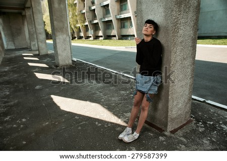 young fit woman with modern haircut. she is in the shade of building. she wears jeans and sweatshirt. She has tattoos throughout her body.  - stock photo